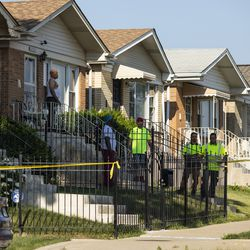 Neighbors watch as Chicago police personnel investigate after an officer shot an alleged suspect inside an apartment in the 6200 block of West Grand Avenue, Monday morning, July 8, 2019.