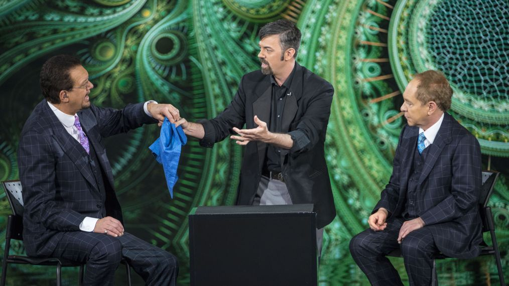 A magician holds a hankerchief with Penn Jillette while Teller watches