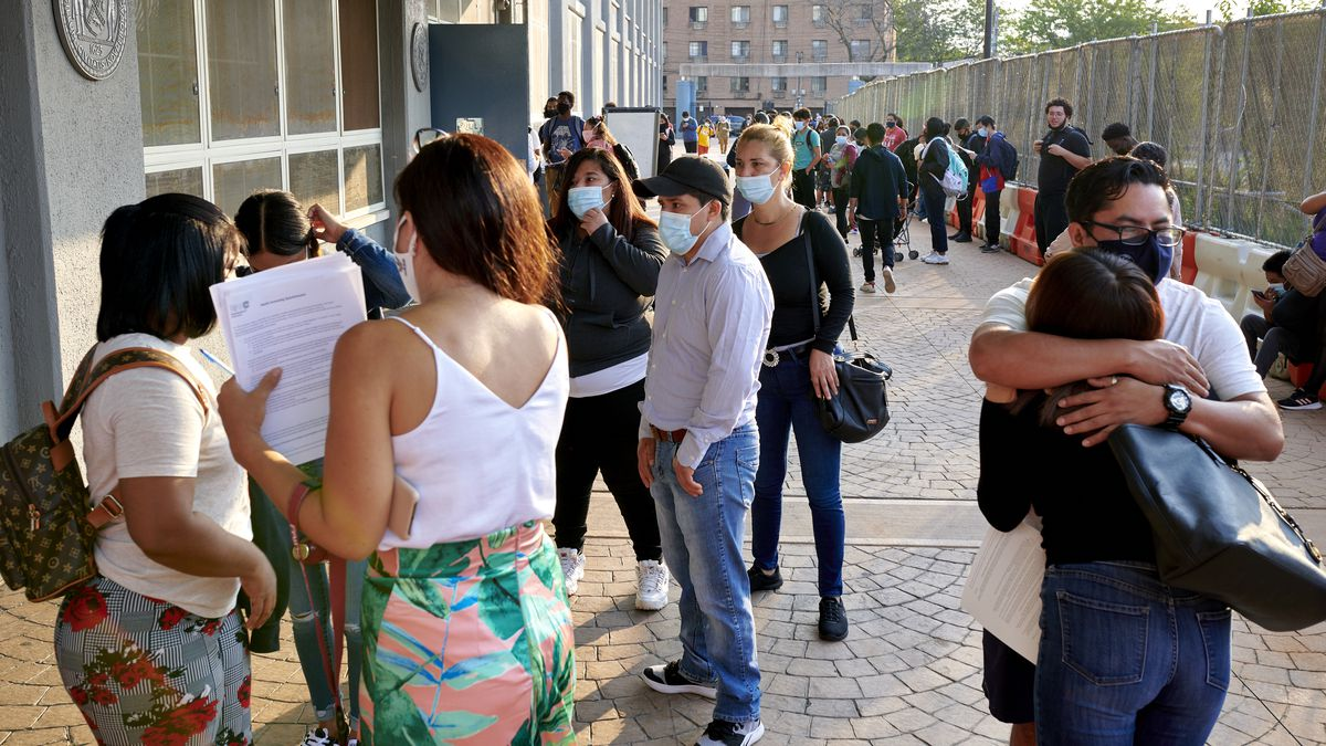 Students embrace as several others make their way into Pan American High School on the first day of classes.