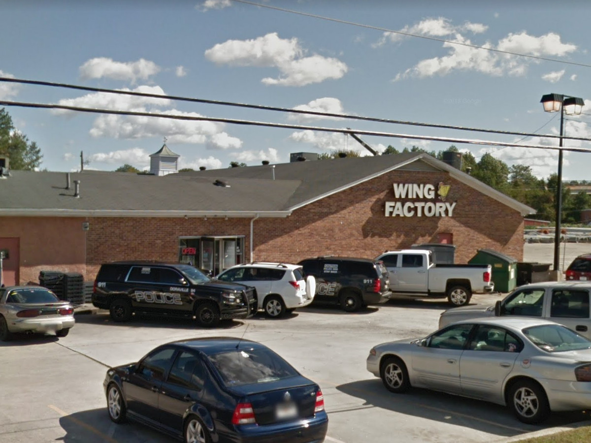 The exterior of a pub restaurant. The building is red brick and has a parking lot in front. There is a sign above the entrance that reads: Wing Factory.