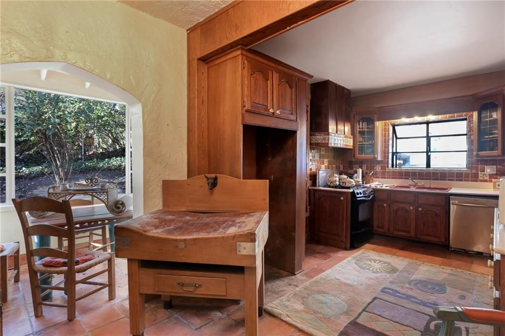 A dated kitchen with brown woods cabinets and a strange table.
