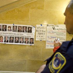 Capital Police officer Greg Friberg of Milwaukee looks a poster on display at the State Capitol in Madison, Wis., Sunday, Feb. 20, 2011. Opponents to the governor's bill to eliminate collective bargaining rights for many state workers are on their sixth day of protesting.