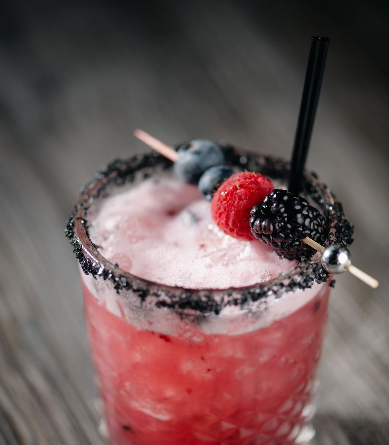 Cocktail topped with berries.