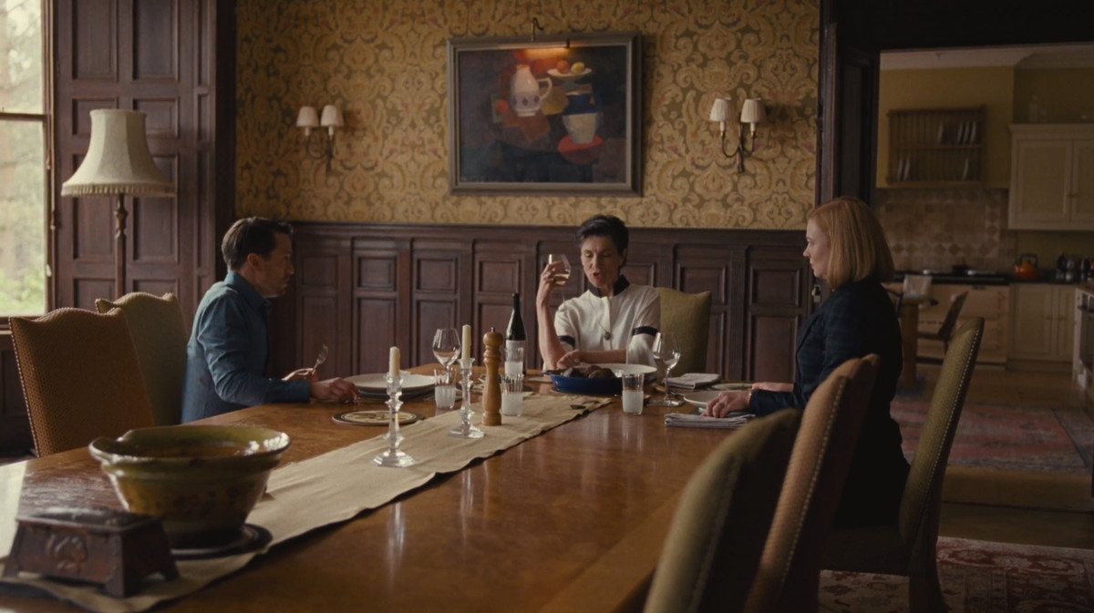 Succession screenshot: Roman, Shiv, and their mother Caroline eating at a dining table in Caroline's England home.