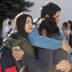 A family hugs as they reunite outside Mountain View High School in Orem on Tuesday, Nov. 15, 2016, after five students were stabbed in an apparent attack by a 16-year-old boy.