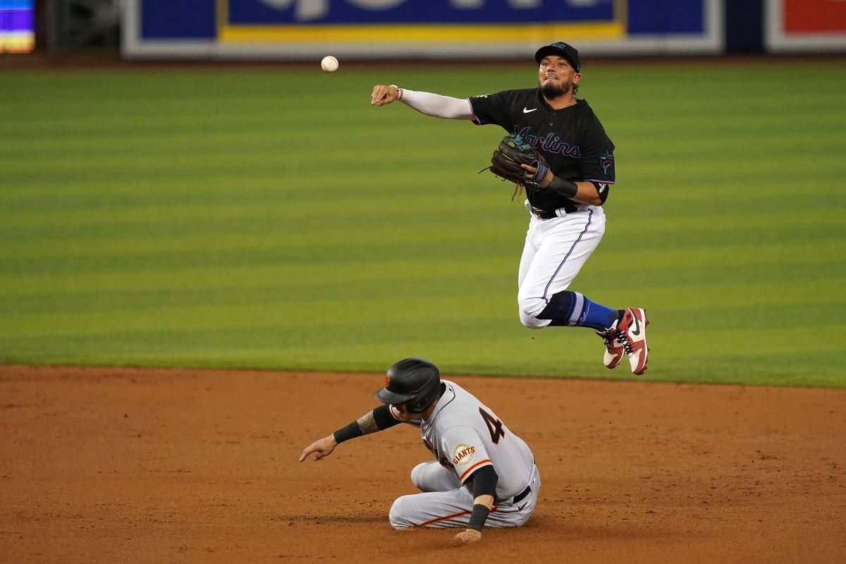 Miami Marlins shortstop Miguel Rojas gets the force out of San Francisco Giants first baseman Wilmer Flores while attempting to turn a double play in the 2nd inning at loanDepot park.