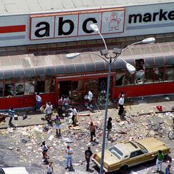 In this April 30, 1992 file photo, looters mill in the parking lot of the ABC Market in South-Central Los Angeles as violence and looting ensued on the first day of riots following the verdicts in the Rodney King assault case. The acquittal of four police officers in the videotaped beating of King sparked rioting that spread across the city and into neighboring suburbs. Cars were demolished and homes and businesses were burned. Before order was restored, 55 people were dead, 2,300 injured and more than 1,500 buildings were damaged or destroyed.