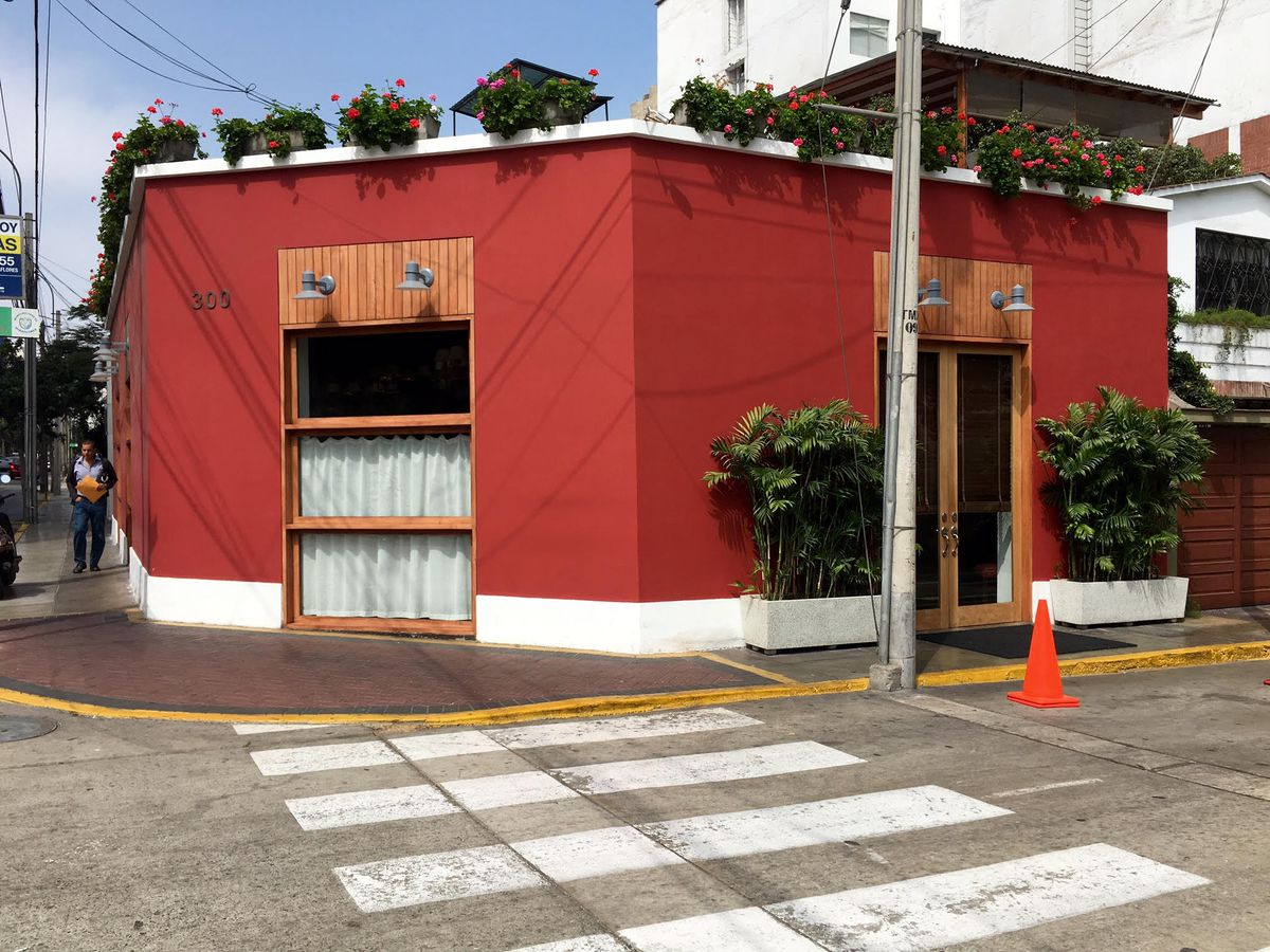 An exterior shot of the Rafael restaurant, a dusty, one-story, red building sitting on a street corner with small bushes and more plants lining the edge of the roof.