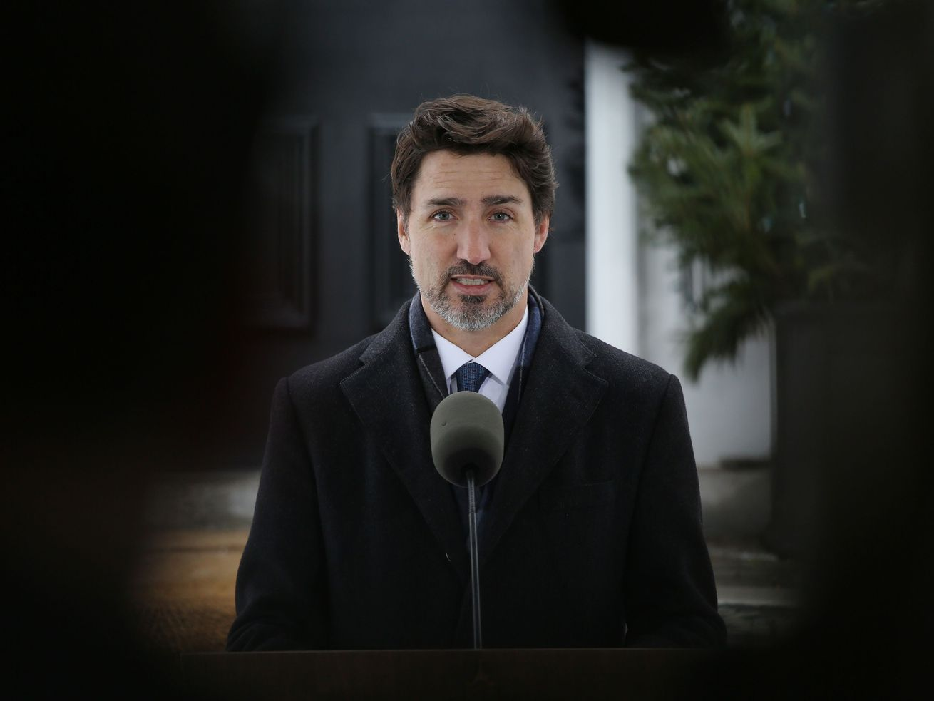 Trudeau, in a black overcoat and blue tie, speaks into a microphone in front of his home, his body framed in the photo by reporters.