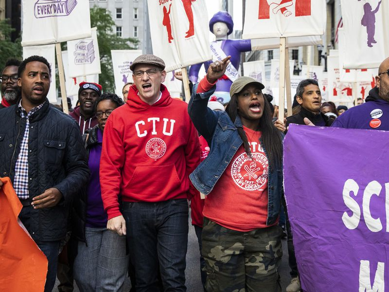 Chicago Teachers Union President Jesse Sharkey (front row, second from left) and Vice President Stacy Davis Gates (third from left) march with members of the CTU and SEIU Local 73 through the Loop after a rally, three days before the unions could walk off the job on strike, Monday afternoon, Oct. 14, 2019.