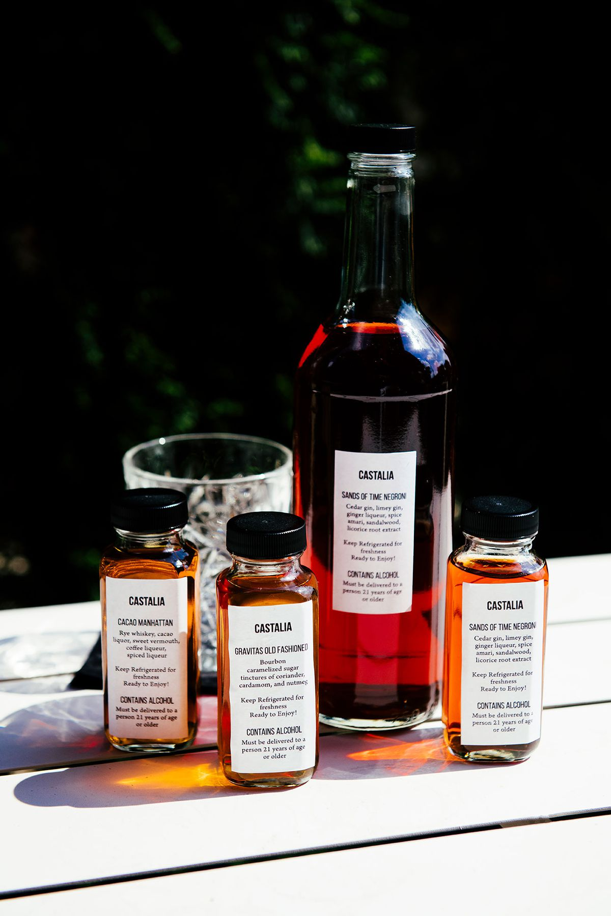 Three small rectangular bottles and a large wine-style bottled cocktail on a patio table.