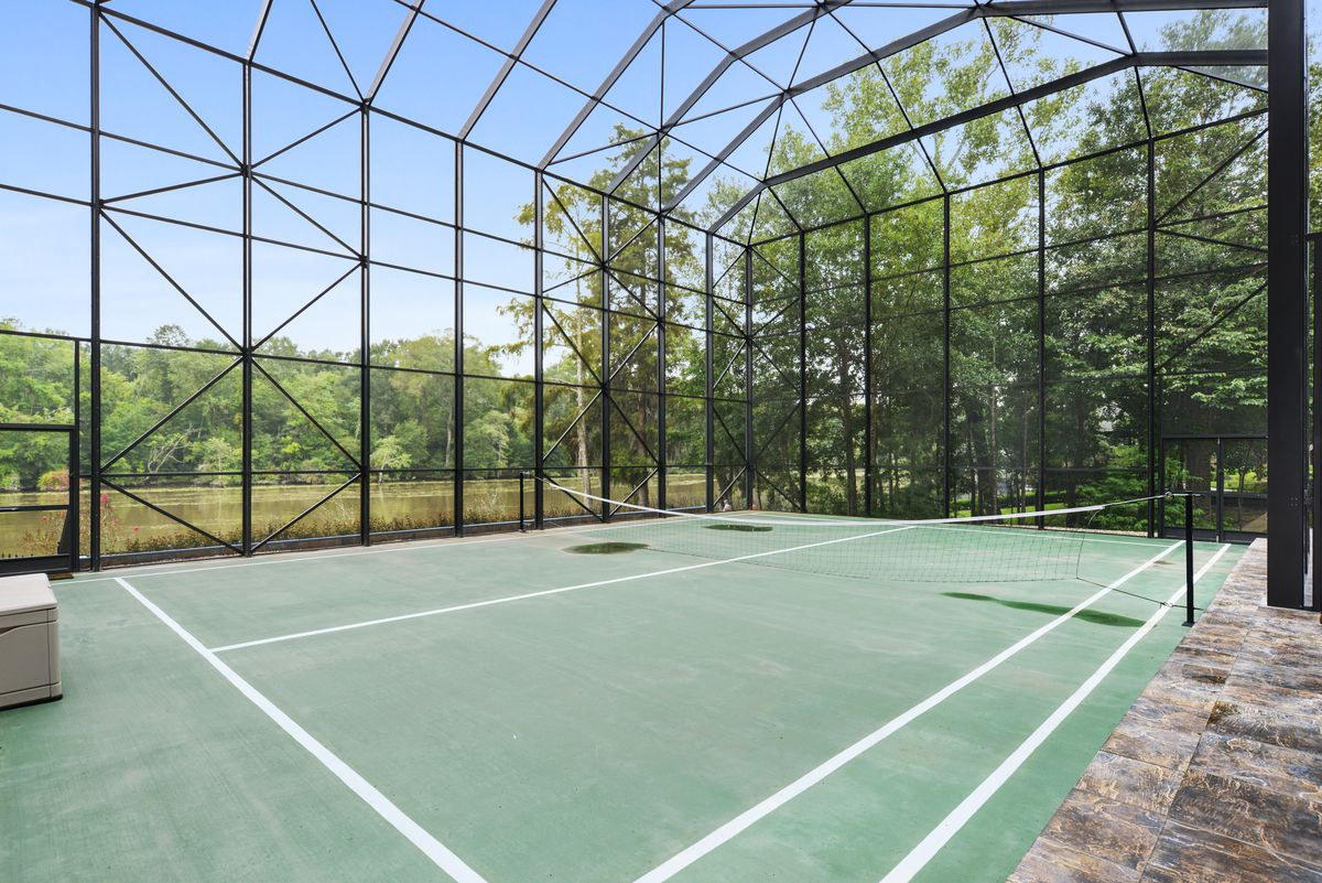 A tennis court by a river and swamp is covered by a soaring screen enclosure.