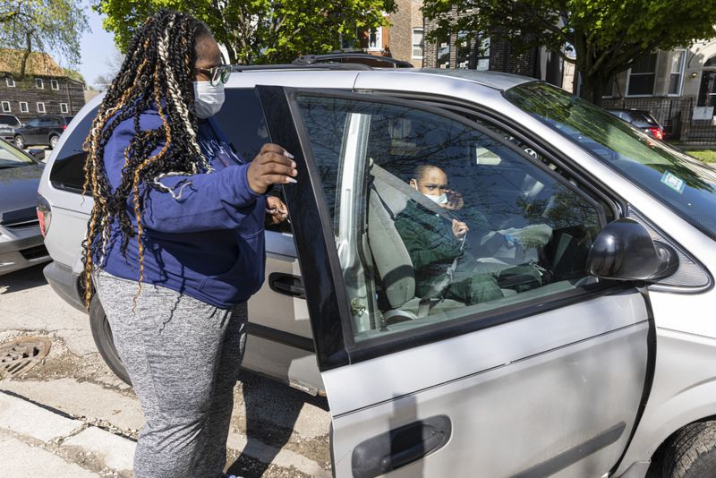 Alanna Barber watches her son Sean Smith, 8, put on his seatbelt outside of Beasley Elementary in Washington Park, Thursday, April 29, 2021.