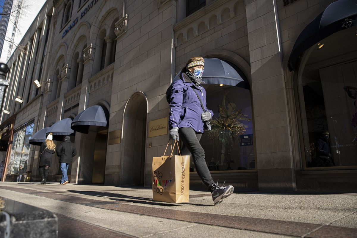 A shopper walks by with a shopping bag on North Michigan in Magnificent Mile, Monday, Dec. 14, 2020.