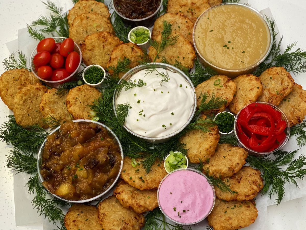 A mountain of herby potato latkes are arranged on a table, alongside sprigs of dill and several colorful dipping sauces