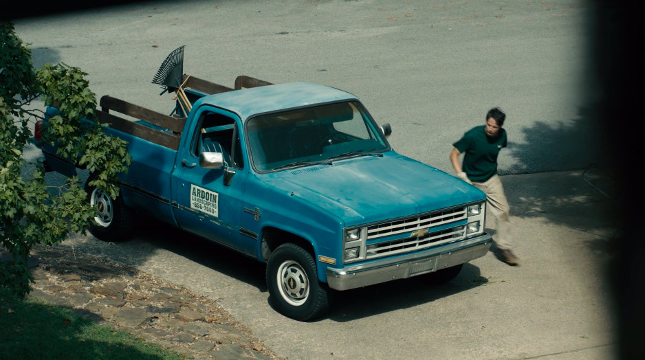 Mike Ardoin walking beside a blue truck for his landscaping business