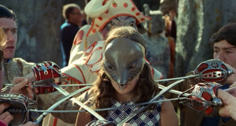 Still from The Wicker Man. Men form a pentagram out of swords with a girl in a mask imprisoned in the center.