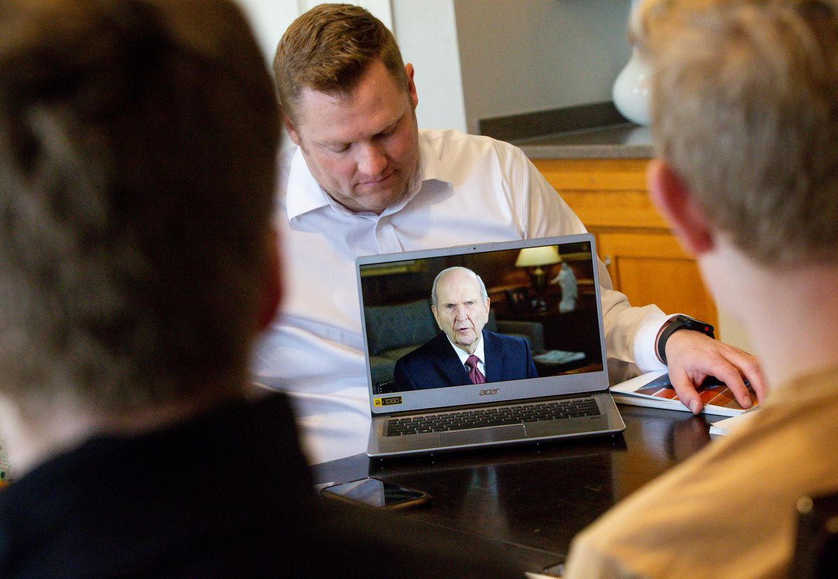 """Ryan Kirby shows his family a video message from President Russell M. Nelson during their gospel study at home using """"Come, Follow Me — For Individuals and Families: Book of Mormon 2020,"""" a manual for The Church of Jesus Christ of Latter-day Saints, in Lehi on Sunday, March 15, 2020. The church temporarily canceled all meetings and activities worldwide to limit public gatherings in response to the coronavirus pandemic."""