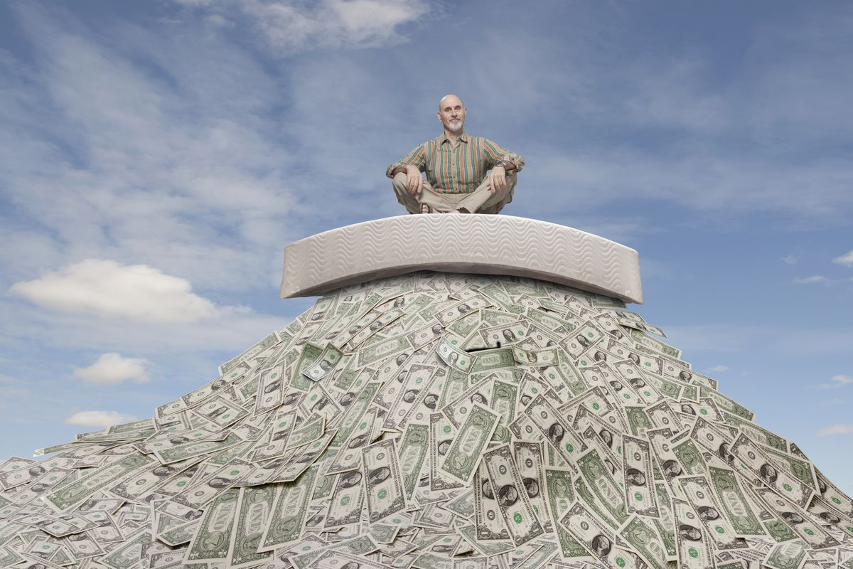 A man sitting atop a pile of cash.