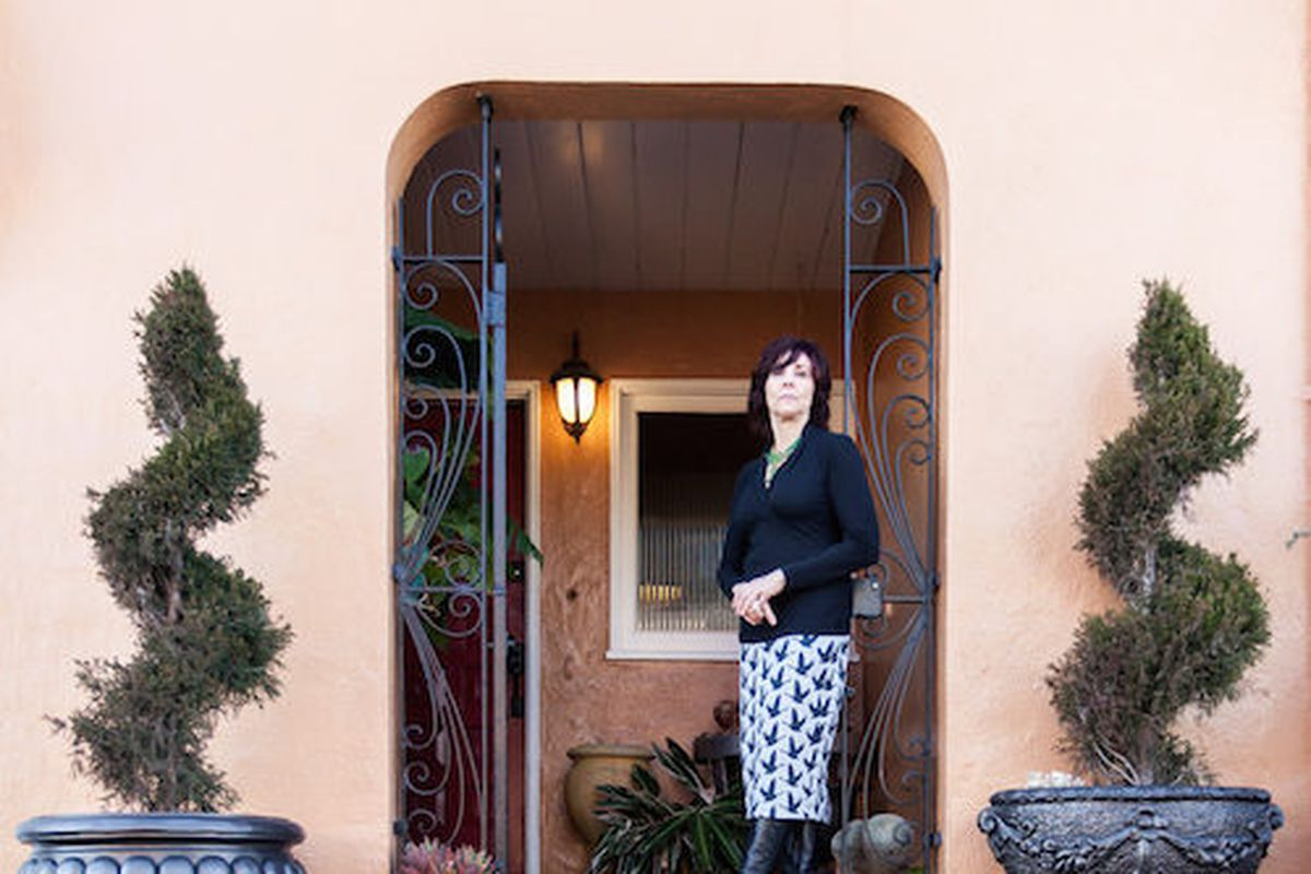 A woman stands in a doorway to a house. The facade is peach and there are two plants in planters on both sides of the doorway. Inside there is a light fixture.