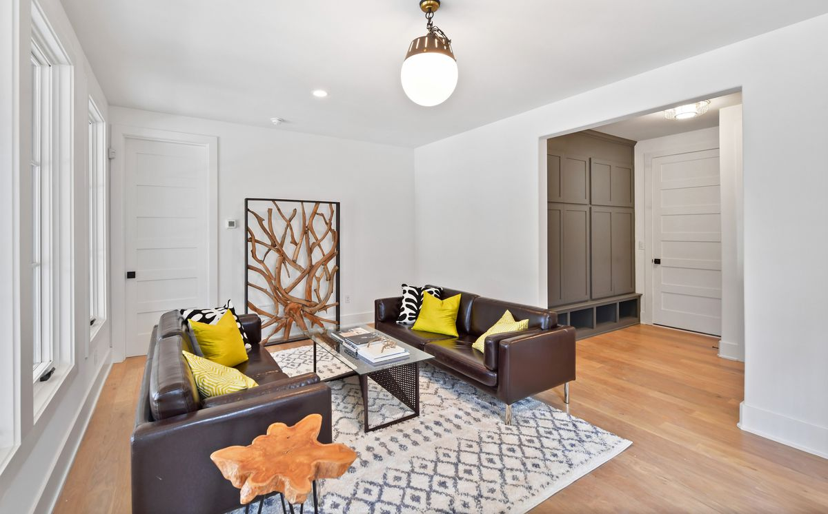 Large room with two couches, a coffee table, an area rug, and built-in storage.