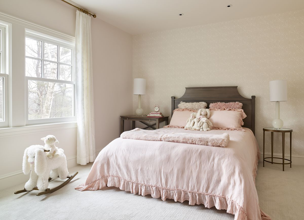 A small bedroom with a monochromatic light pink color scheme. White toys lay on the floor and the bed.