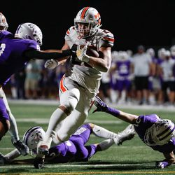 Timpview's Carsen Ryan (20) carries the ballagainst the Lehi defense during a high school football game at Lehi High School in Lehi on Friday, Sept. 25, 2020.