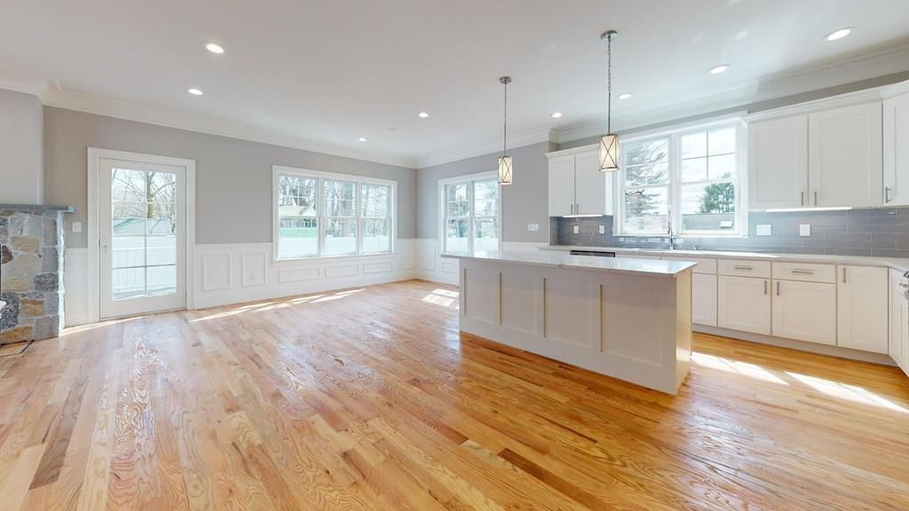 An empty dining room-open kitchen area with an island.