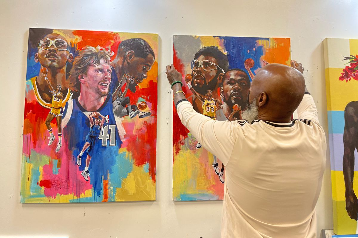 a photo of artist Charly Palmer putting up a painting of Kareem Abdul-Jabbar, Kevin Durant, and Dirk Nowitzki next to a similar painting