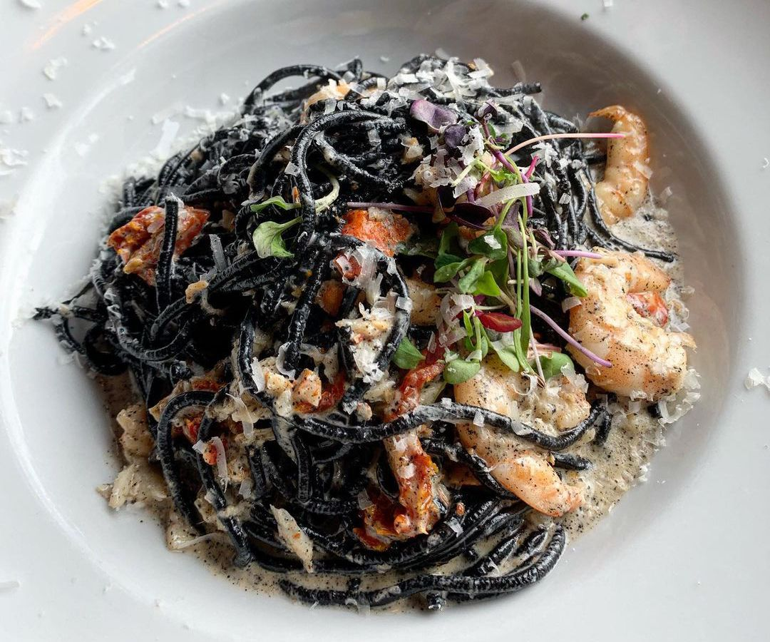 A plate of black noodles with shrimp and lobster chunks visible through the strands, along with herbs and diced vegetables