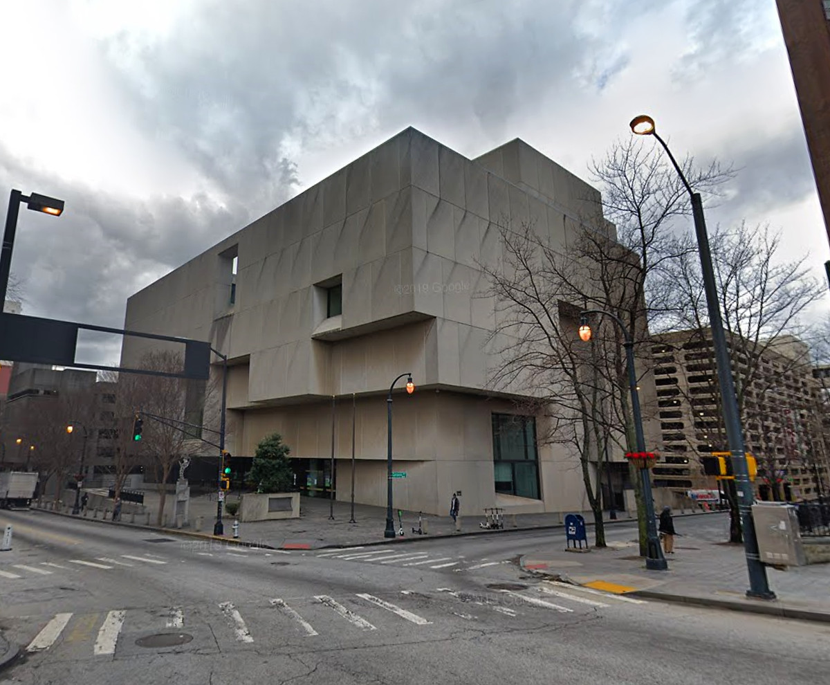 A picture of the beefy, grey concrete block of a library, surrounded on all sides by aging city streets.