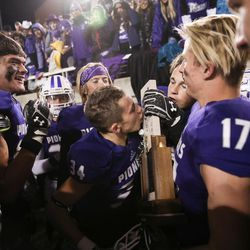 Lehi's Trent Kendall kisses the trophy as Lehi celebrates their 55-17 win over Skyridge in the 5A football state championship game at Rice-Eccles Stadium in Salt Lake City on Friday, Nov. 17, 2017.