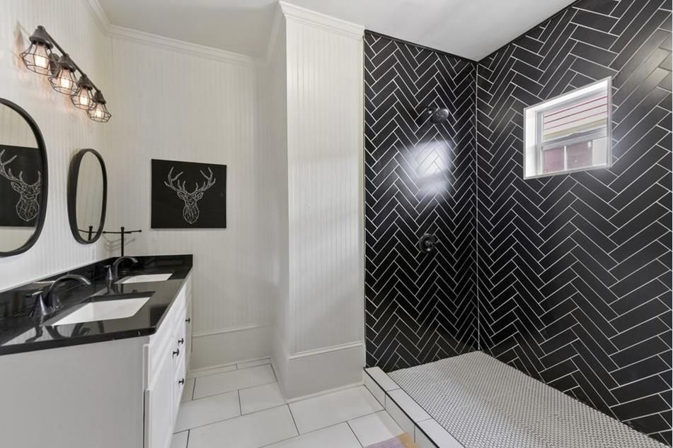 A white bathroom with black tile.