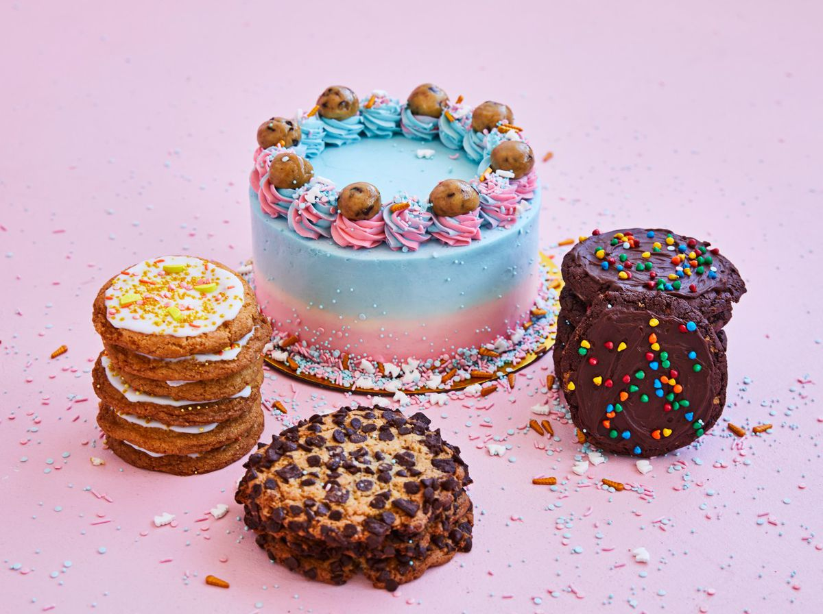 bright blue cake surrounded by stacks of cookies on a pink table