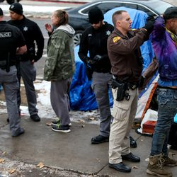 A Utah Highway Patrol trooper arrests a man where a number of people who are homeless are camped on 300 East at Library Square in Salt Lake City on Wednesday, Nov. 27, 2019.