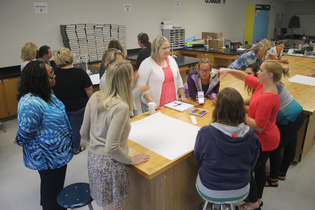 Karyn Bailey (left), a facilitator from Williamson County Schools, coaches elementary school teachers during a 2017 exercise on Tennessee's revised standards for English language arts as part of a two-day training at La Vergne High School, one of 11 training sites across the state.