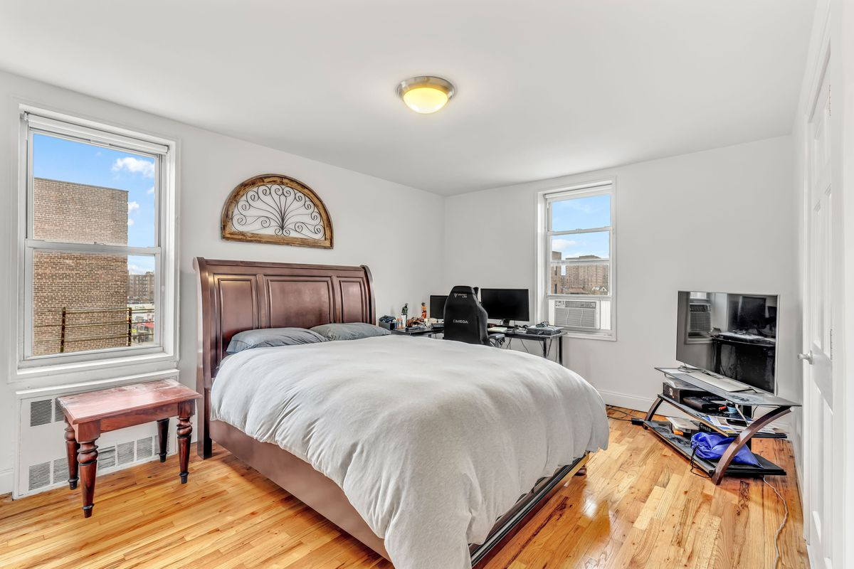 A bedroom with a large bed, hardwood floors, and two windows.