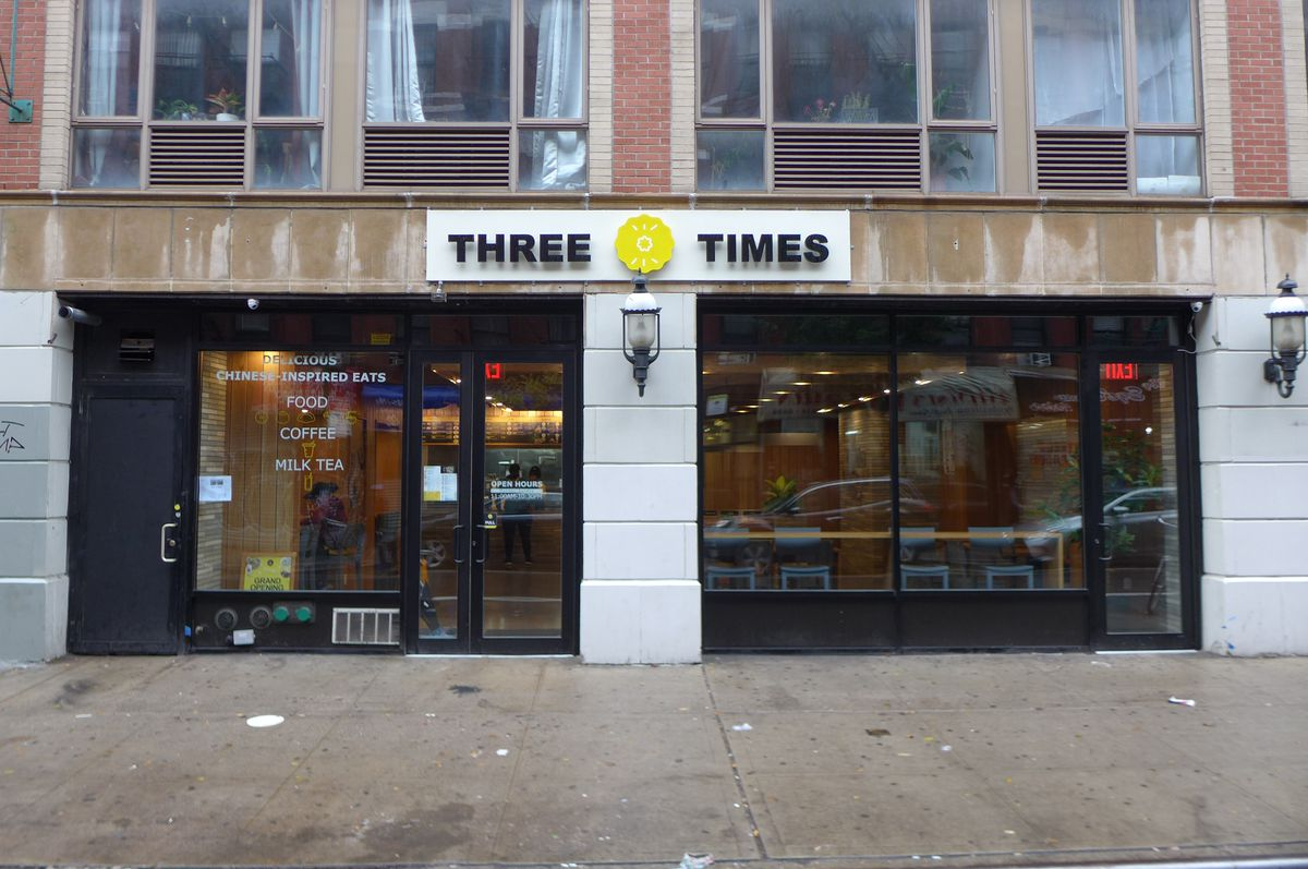 A double storefront has darkened windows and a sign above the middle that reads 3 Times...