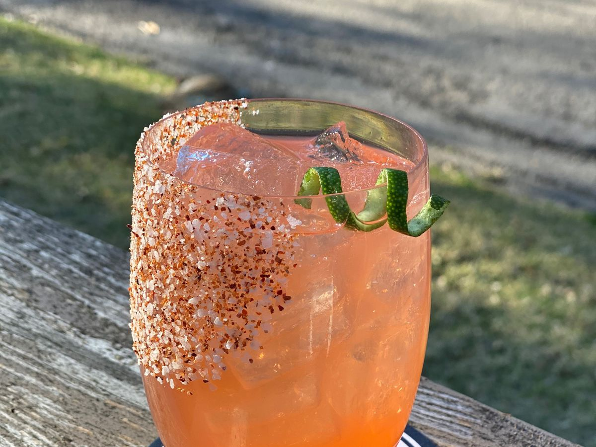 The light pink Watermelonade at The Yard, in a stemless wine glass, garnished with jalapeno swirls and salt on the rim.