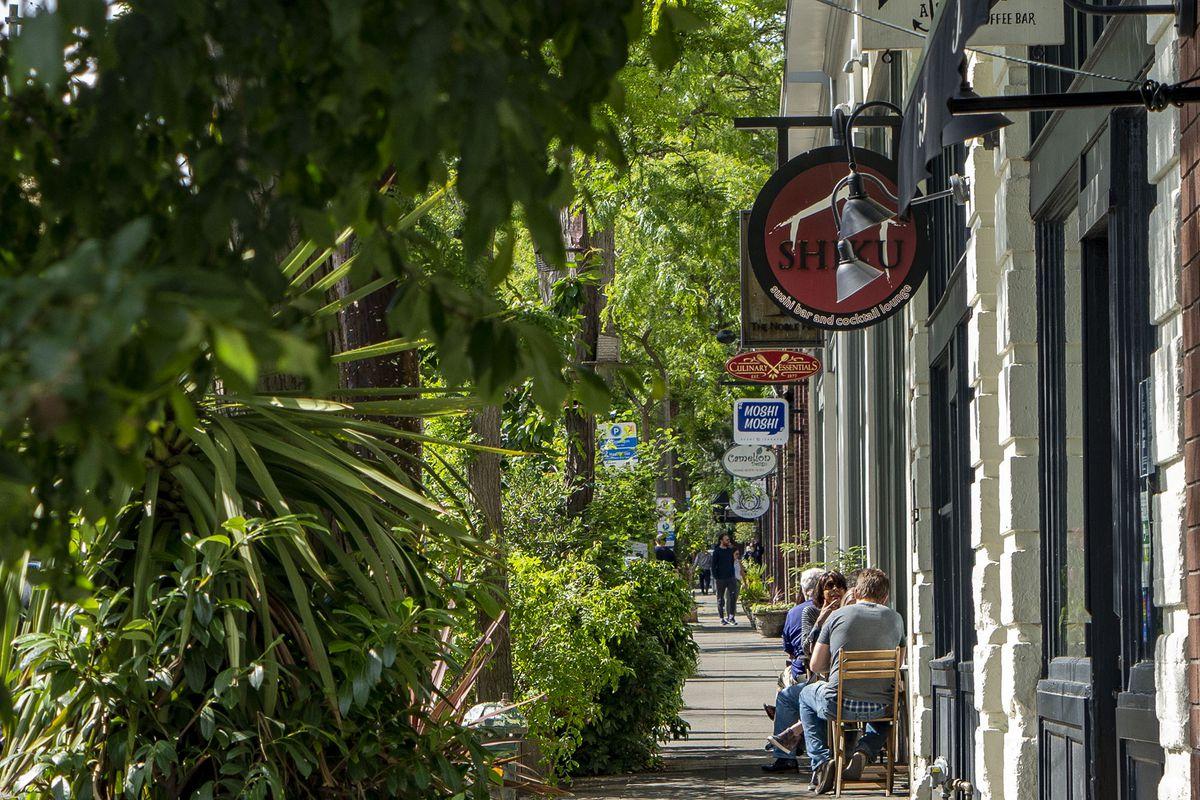 Sidewalk seating outside a restaurant in Seattle's Ballard neighborhood on a sunny day