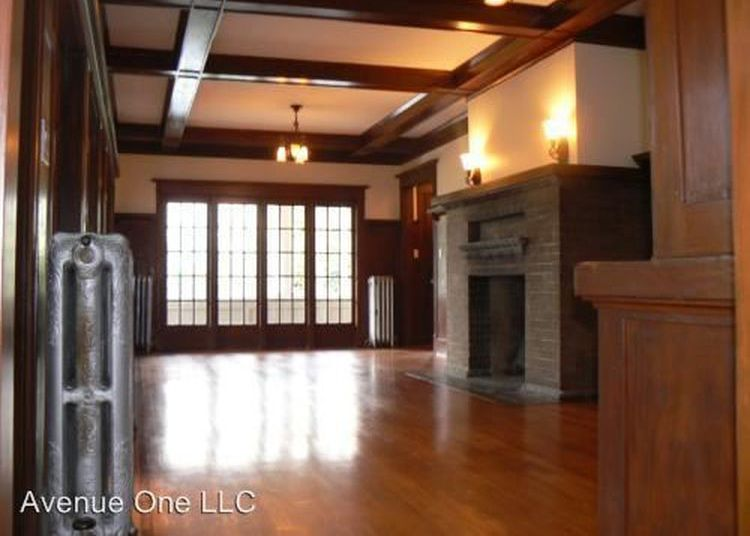 The interior of an apartment has hardwood floors, boxbeam ceilings, a fireplace, and floor to ceiling leaded glass windows