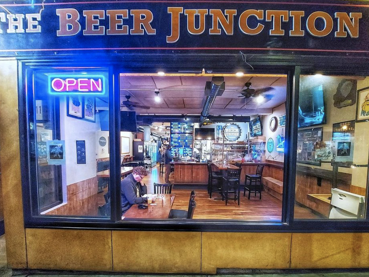 """The front of the Beer Junction in West Seattle, with a lighted neon sign that says """"open"""""""