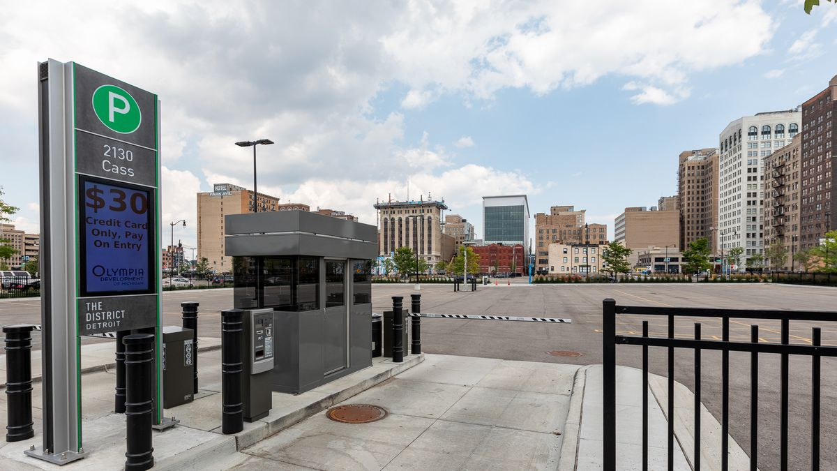 """A swinging gate leads to an empty concrete parking lot. A nearby screen says """"$30."""" Many buildings are in the distance."""