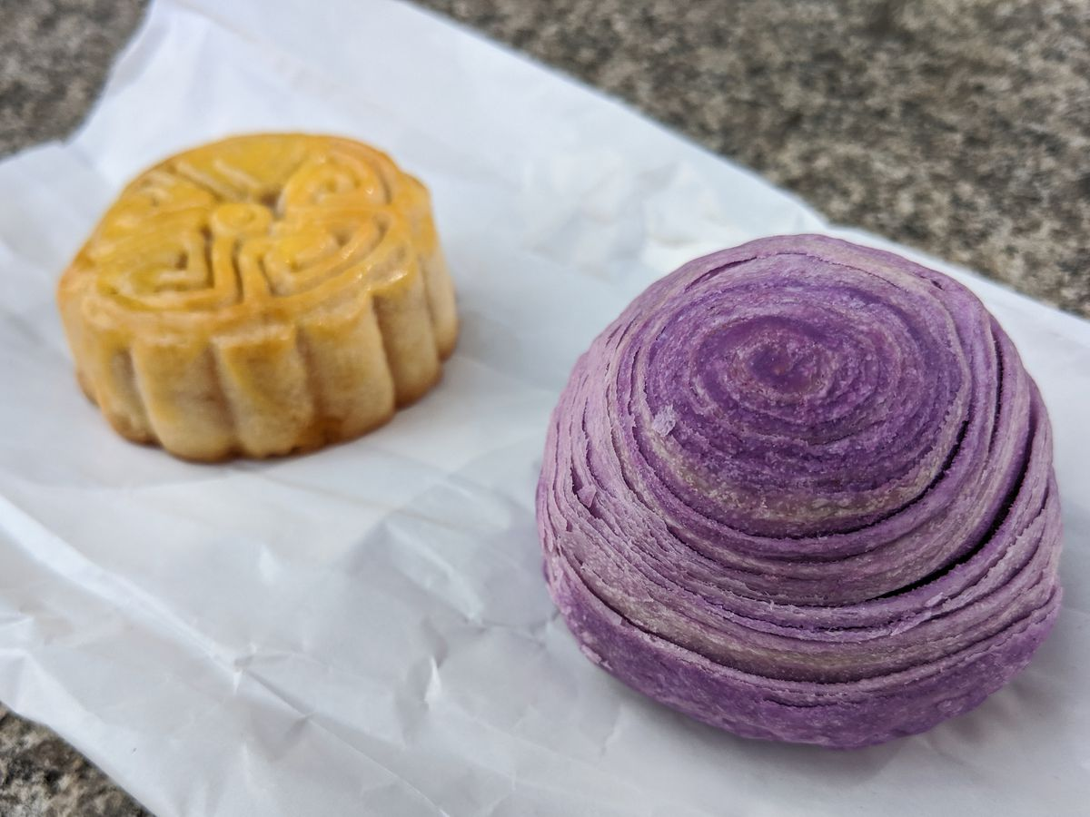 A swirled purple pastry made of taro and a small glossy mooncake sit on a white paper bag on a stone background