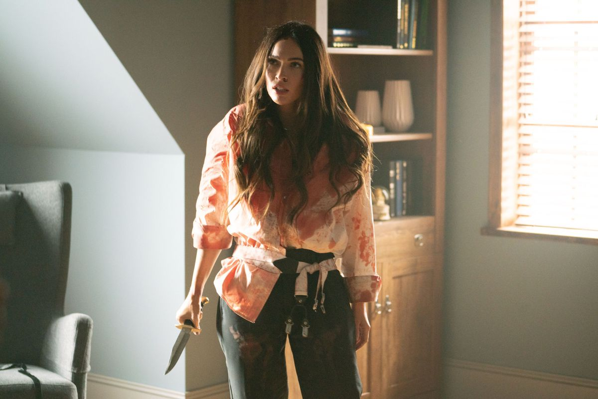 Megan Fox as Emma, covered in blood and brandishing a knife in Till Death