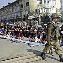 An Indian soldier patrols as Kashmiri Muslims offer prayers on the second Friday of Ramadan in Srinagar.