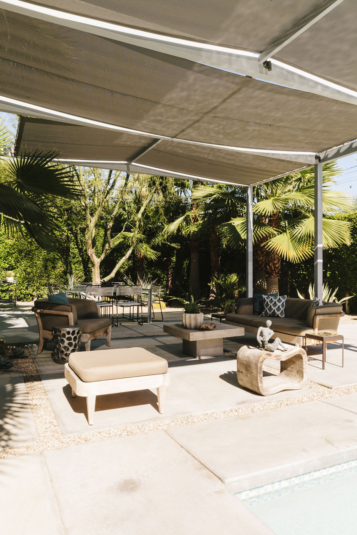 An outdoor patio. There are multiple chairs and a table. Above the patio is a sun shade. The patio is surrounded by palm trees.