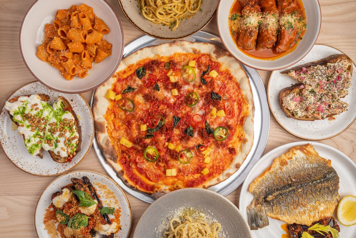 A thin, crispy pizza and sides like toast from above at a restaurant.