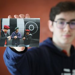 In this photo taken on Tuesday, May 5, 2020, Jonas Rocand, 14, shows of photo of him and friends in front of a World War II era plane. As V-E Day approached, students in the Normandy region thought of 94-year-old veteran Bill Ridgewell and other vets living in isolation because of the COVID-19 pandemic — just as they were. The teens decided to swap stories with the men about their lives under lockdown.