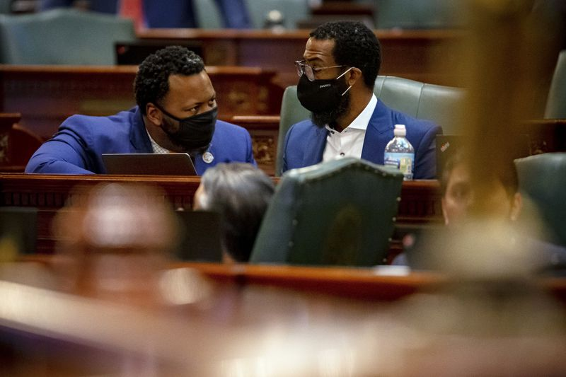 State Rep. Kam Buckner, D-Chicago, left, talks with fellow state Rep. Curtis Tarver, D-Chicago, on the floor of the Illinois House of Representatives on the last day of s spring session.